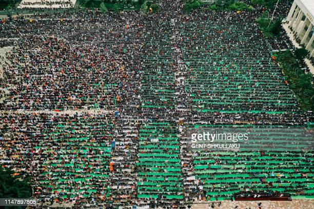 This aerial photo taken on June 4 shows Albanian Muslims praying at Skenderbej square on the first day of the Muslim festival marking the end of the...