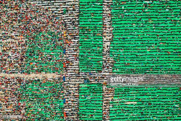 TOPSHOT This aerial photo taken on June 4 shows Albanian Muslims praying at Skenderbej square on the first day of the Muslim festival marking the end...