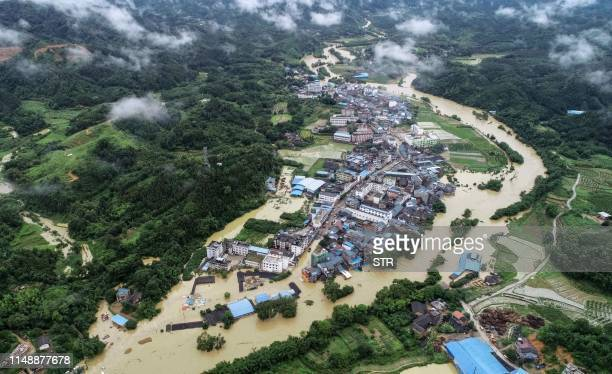 This aerial photo taken on June 9 2019 shows a general view of submerged buildings and roads after heavy rain caused flooding in Rongan in China's...