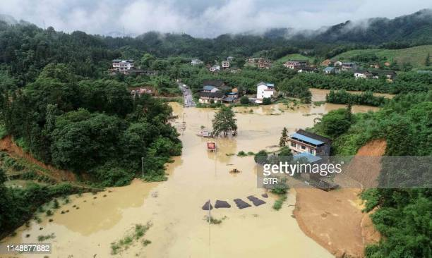 TOPSHOT This aerial photo taken on June 9 2019 shows a general view of submerged buildings after heavy rain caused flooding in Rongan in China's...