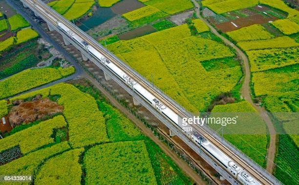 This aerial photo taken on March 16 2017 shows a highspeed train traveling on the railway in Anshun southwest China's Guizhou province / AFP PHOTO /...