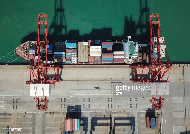 This aerial photo taken on May 8 2019 shows a cargo ship berthing at a port in Lianyungang in China's eastern Jiangsu province China's exports fell...