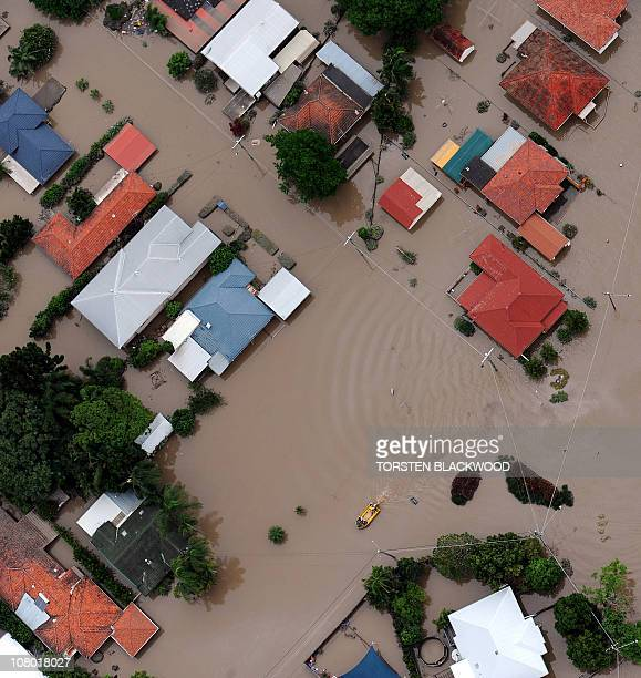 This aerial photograph shows a boat travelling down a suburban street as flood waters devastate much of Brisbane on January 13 2011 Australia's...