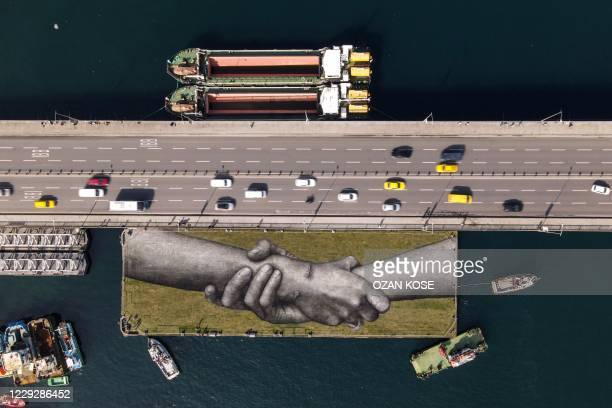 This aerial photograph shows a giant biodegradable land art painting by French artist Guillaume Legros, aka Saype, representing two hands clasped...