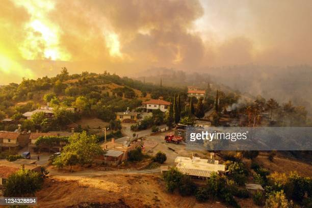 This aerial photograph shows houses surrounded by a wildfire which engulfed a Mediterranean resort region on Turkey's southern coast near the town of...