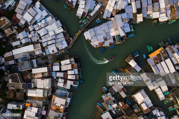 This aerial photograph taken on February 20, 2020 shows a boat moving past houses in Tai O village in Hong Kong.