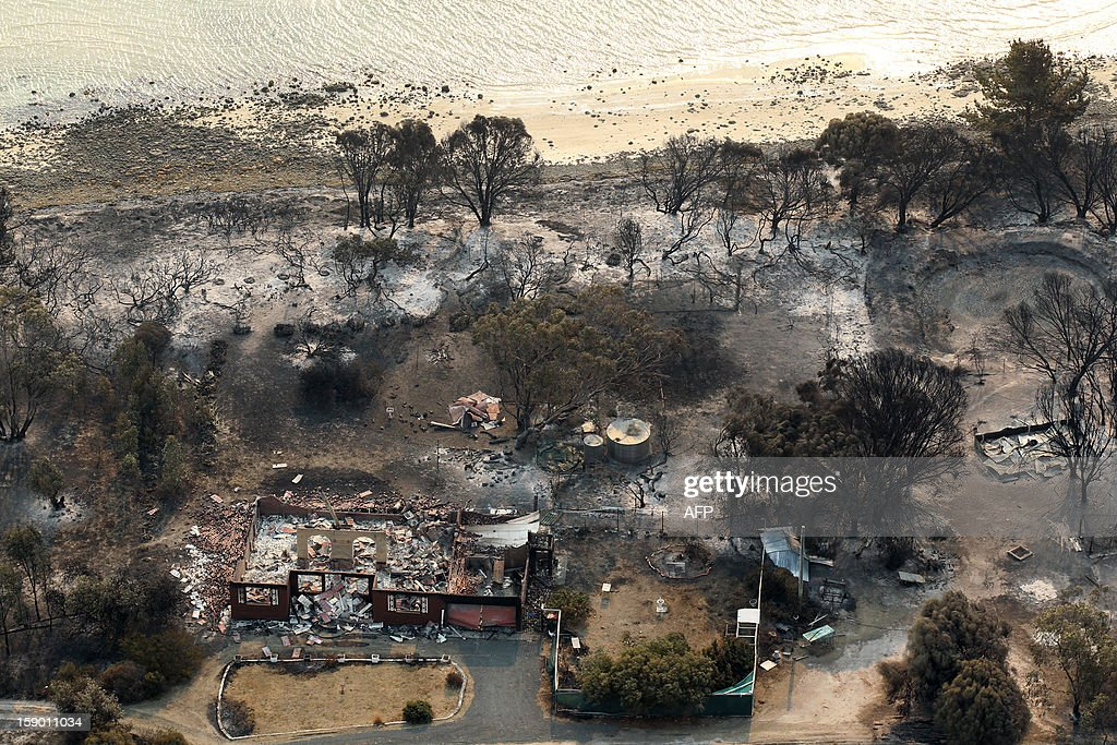 This aerial photograph taken on January 5, 2013 shows the devastated area Boomer Bay after bush fires swept through the area. Thousands of people have fled wildfires raging on the Australian island of Tasmania that have destroyed at least 80 properties amid fears that at least one man died in the blaze, police said. AFP PHOTO / POOL / Chris Kidd