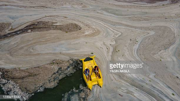This aerial photograph taken on June 12 in the Darica district of Kocaeli, Turkey, shows a pedalo sailing among the Marmara sea covered with sea...