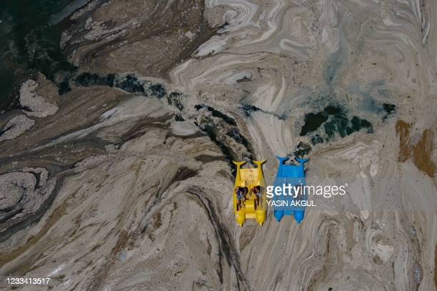 This aerial photograph taken on June 12 in the Darica district of Kocaeli, Turkey, shows pedalos sailing among the Marmara sea covered with sea snot,...