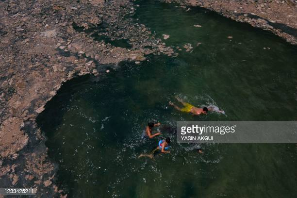 This aerial photograph taken on June 12 in the Darica district of Kocaeli, Turkey, shows children swimming in the Marmara sea covered with sea snot,...