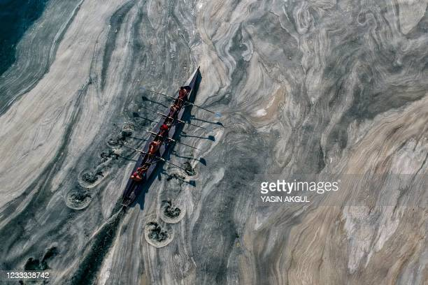 This aerial photograph taken on June 8, 2021 on the Caddebostan shore of Turkey's Marmara Sea, shows a boat sailing among mucilage, a jelly-like...