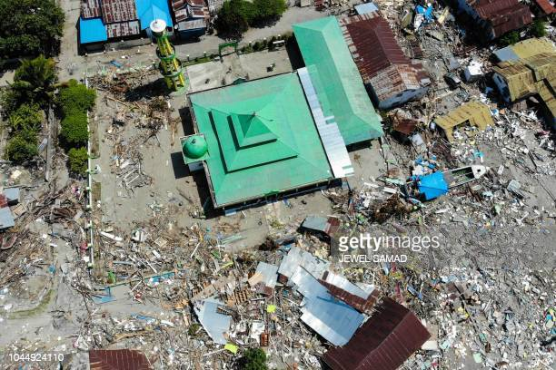 TOPSHOT This aerial photograph taken on October 3 2018 shows devastation after tsunami waves swept through coastal houses and buildings in Wani...