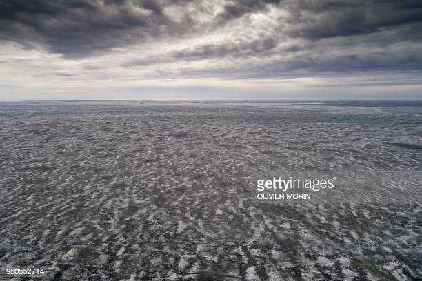 TOPSHOT This aerial picture shows melting frozen sea during warm temperatures at the beginning of spring on April 23 in Raipaluoto island western...