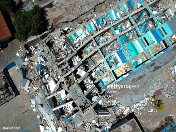 This aerial picture shows the remains of a tenstorey hotel in Palu in Indonesia's Central Sulawesi on September 30 2018 after it collapsed following...