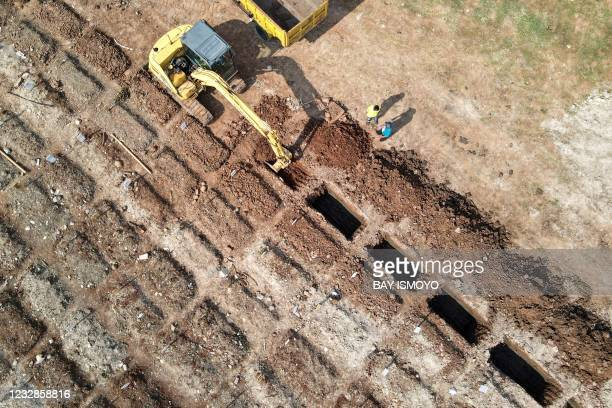 This aerial picture shows workers digging grave sites at a burial location for victims of the COVID-19 coronavirus in Jakarta on May 13, 2021.