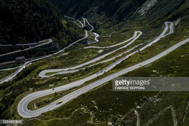 TOPSHOT This aerial picture taken on August 28 2018 from above Gletsch shows bicycles motorcycle and car making their way to the Grimsel Pass a...