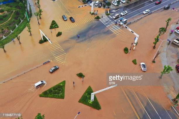 This aerial picture taken on July 9, 2019 shows submerged streets after heavy rain caused flooding in Hengyang in central China's Hunan province. /...