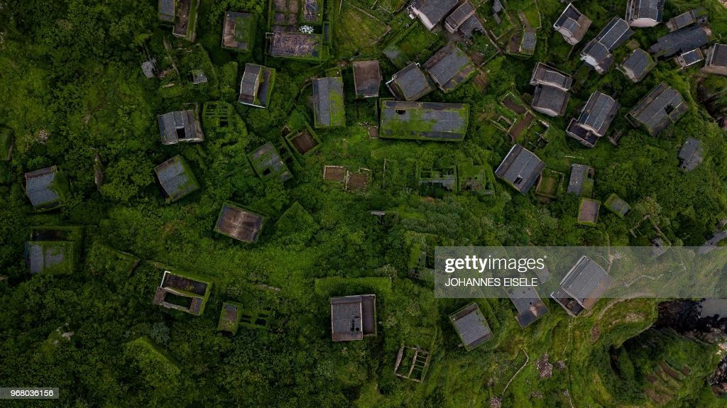 TOPSHOT - This aerial picture taken on May 31, 2018 shows abandoned village houses covered with overgrown vegetation in Houtouwan on Shengshan island, China's eastern Zhejiang province. - Houtouwan was a thriving fishing community of sturdy brick homes that climb up the steeply hilled island of Shenghshan, but is now abandoned, with entire houses completely overgrown as if vacuum-sealed in a lush layer of green.