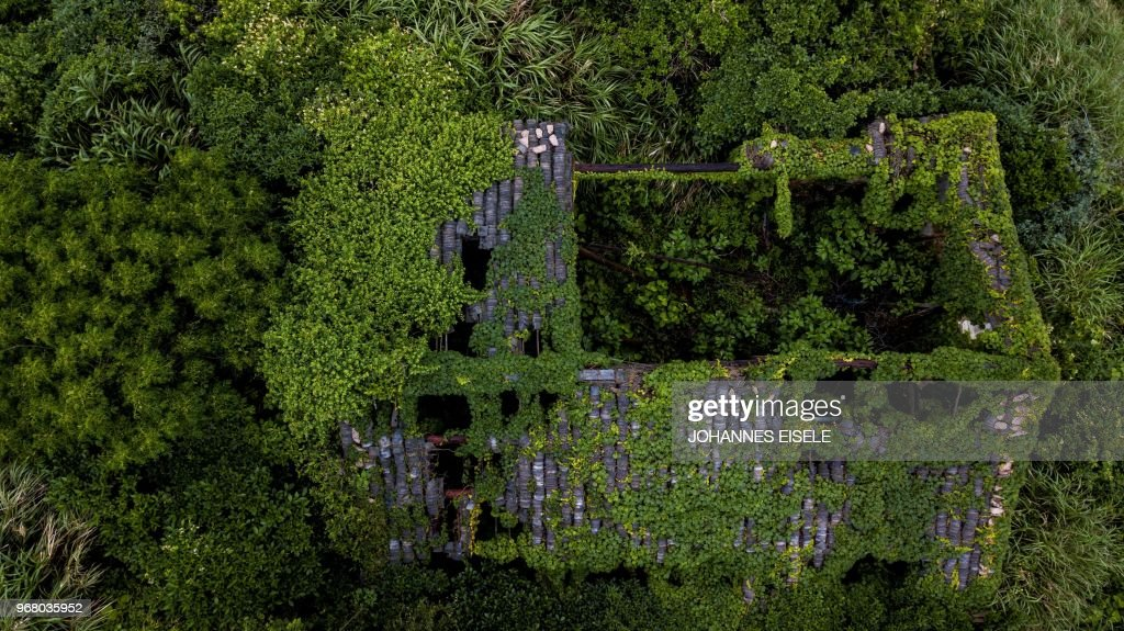 This aerial picture taken on May 31, 2018 shows an abandoned village house covered with overgrown vegetation in Houtouwan on Shengshan island, China's eastern Zhejiang province. - Houtouwan was a thriving fishing community of sturdy brick homes that climb up the steeply hilled island of Shenghshan, but is now abandoned, with entire houses completely overgrown as if vacuum-sealed in a lush layer of green.