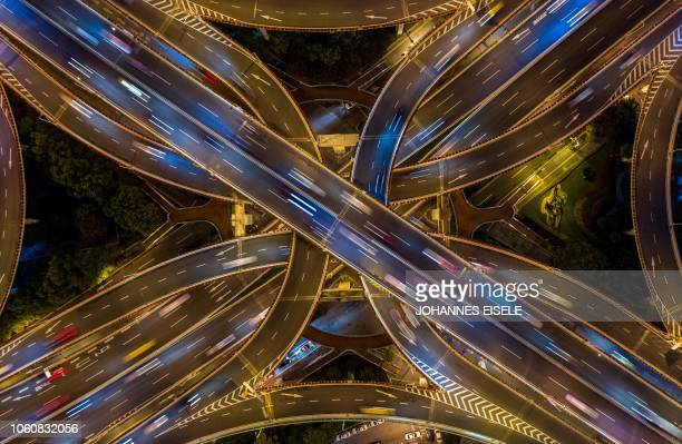 TOPSHOT This aerial picture taken on the night of November 12 2018 shows traffic on an elevated intersection in downtown Shanghai