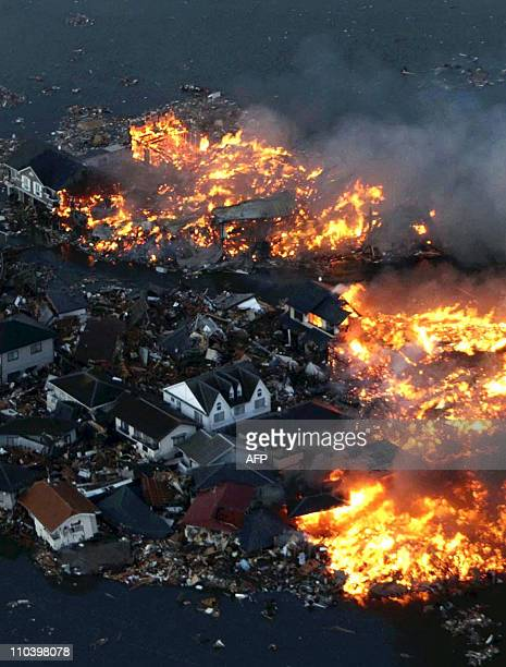 This aerial shot shows houses in flame after being hit by a tsunami at Natori city in Miyagi prefecture northern Japan on March 11 2011 A massive...