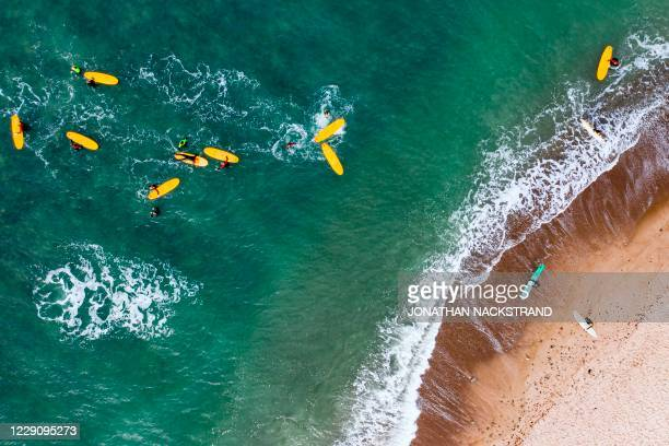 This aerial view image shows surfers from a local Surf Camp gather around their instructor ahead of a surfing session on September 30, 2020 in...
