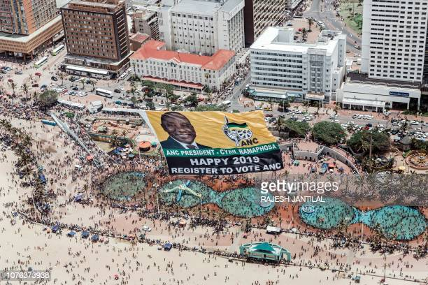 TOPSHOT This aerial view shows a helicopter flying a giant flag from the South African ruling Party African National Congress displaying a picture of...