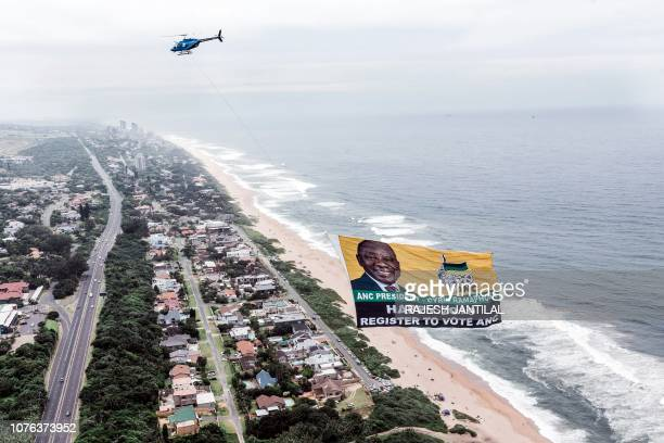 This aerial view shows a helicopter flying a giant flag from the South African ruling Party African National Congress displaying a picture of South...