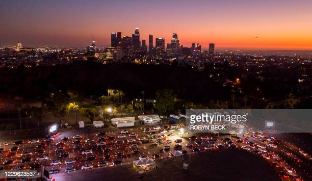 This aerial view shows cars lined up at the Dodger Stadium parking lot for Covid-19 testing with the downtown Los Angeles skyline in the distance, in...