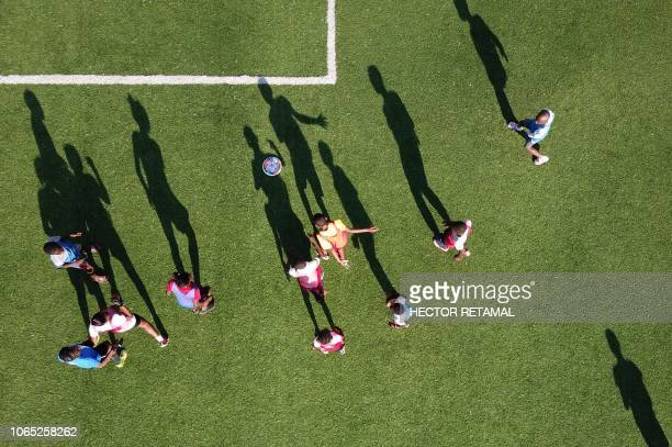 TOPSHOT This aerial view shows children playing frisbee in the Parc Sportif de Bristout in the commune of Petion Ville in the Haitian capital...