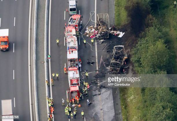 This aerial view shows fire fighters at work at the scene where a tour bus burst into flames following a collision with a trailer truck on highway A9...