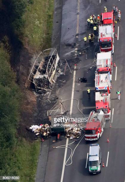 This aerial view shows firefighters at work at the scene where a tour bus burst into flames following a collision with a trailer truck on the highway...