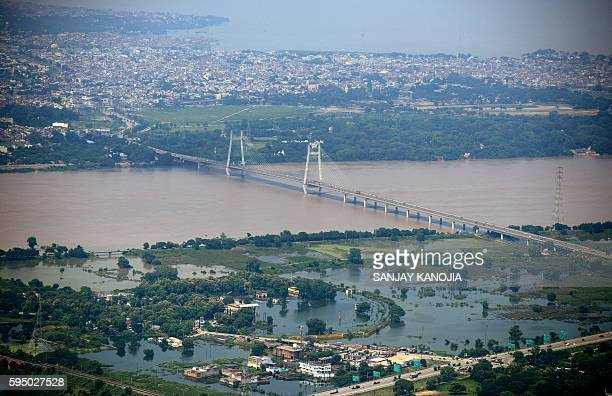 This aerial view shows flooding in low lying areas beside the River Ganges in Allahabad on August 25 2016 At least nine people have died in Uttar...