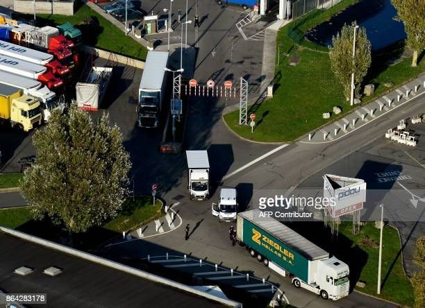 This aerial view shows French police officers control a truck on October 14 2017 by a petrol station near the former 'Jungle' migrant camp that was...