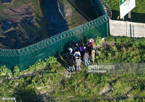 This aerial view shows migrants gather on October 14 2017 by a petrol station's fence near the former 'Jungle' migrant camp that was evacuated 12...