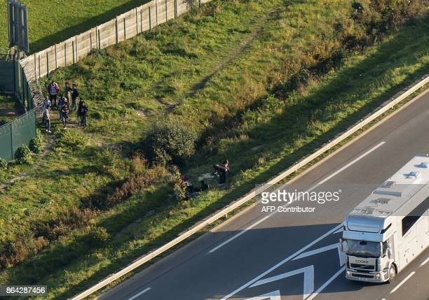 This aerial view shows migrants gather on October 14 2017 by a petrol station's fence as a trucks drives towards the Calais ferry terminal on the...