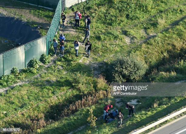 This aerial view shows migrants gather on October 14 2017 by a petrol station's fence along the A216 highway near the former 'Jungle' migrant camp...