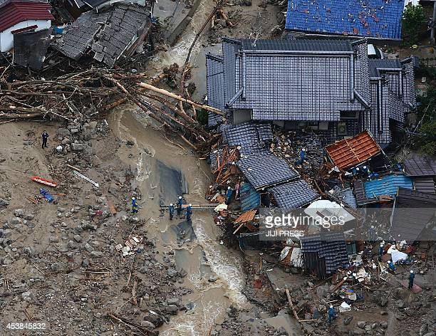 This aerial view shows rescue workers looking for survivors at the site of a landslide after heavy rains hit the city of Hiroshima western Japan on...