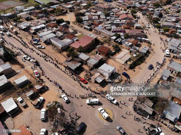 This aerial view shows residents of the Olievenhoutbosch township in Centurion queueing on May 2, 2020 during a food distribution organised by the...