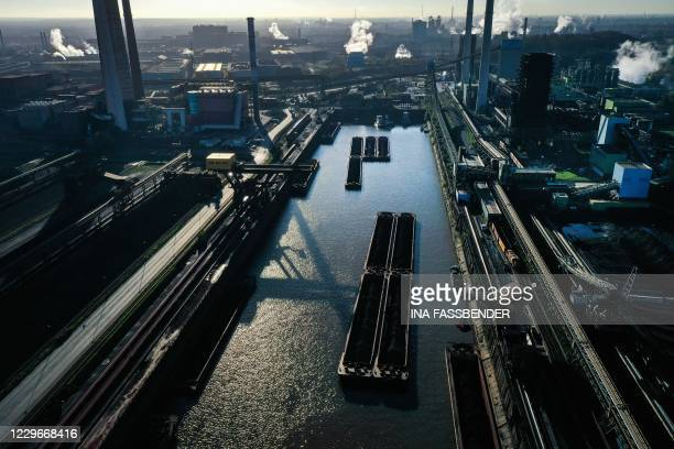 This aerial view shows tanks with coal at the harbour at the plant of German industrial conglomerate ThyssenKrupp in Duisburg, western Germany, on...