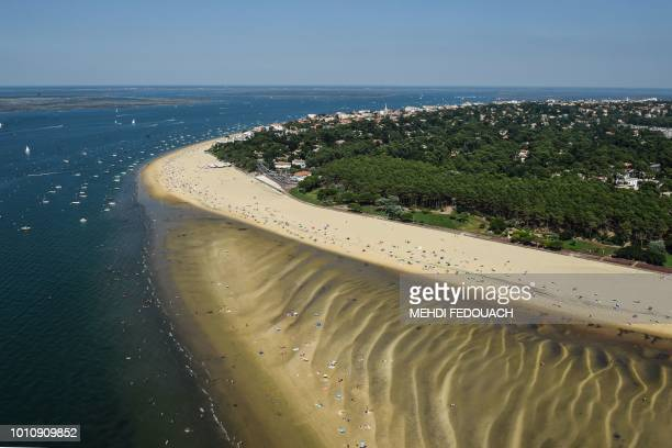 This aerial view shows the shores of Arcachon with people enjoying the beach and small boats sailing on August 4 southwestern France