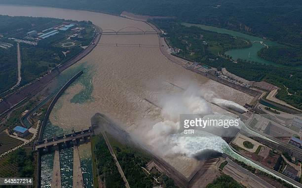 This aerial view shows water being released from the floodgates of the Xiaolangdi dam on the Yellow River near Luoyang in China's Henan province on...