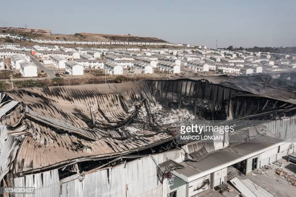 This aerial view taken in Durban, on July 20, 2021 shows the smouldering remains of a warehouse at the Ushukela Industrial Park. - Industrial...