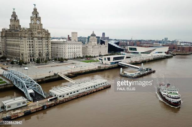 This aerial view taken in Liverpool, north west England on October 2 shows a Mersey Ferry pulling away from Pier Head, near the Liver Building, as it...