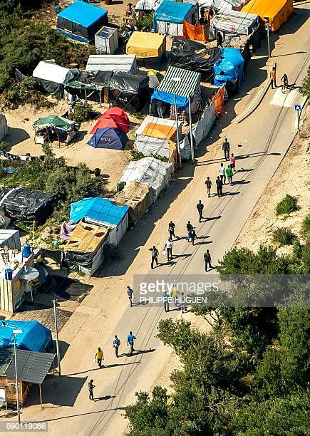 This aerial view taken on August 16 in Calais northern France shows tents and people walking in the jungle camp where over 9000 migrants live...