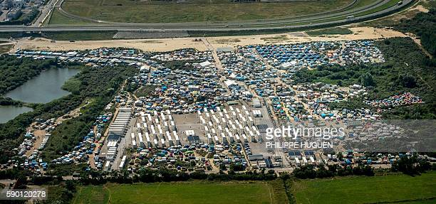 This aerial view taken on August 16 in Calais northern France shows the jungle camp where over 9000 migrants live according to different NGOs Some...