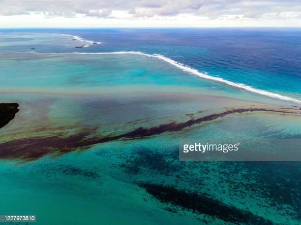 This aerial view taken on August 6, 2020 shows a large patch of leaked oil and the vessel MV Wakashio, belonging to a Japanese company but...
