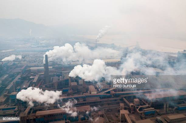 TOPSHOT This aerial view taken on February 17 2018 with a drone shows pollution being emitted from steel factories in Hancheng Shaanxi province / AFP...