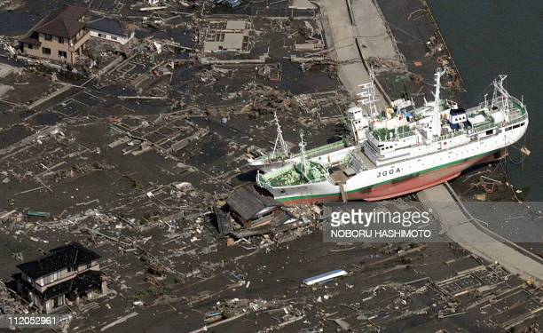 This aerial view taken on March 14 2011 during an AFPchartered flight shows a boat washed ashore crushing a home near Sendai in Miyagi prefecture...