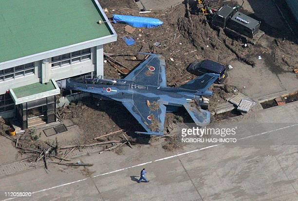 This aerial view taken on March 14 2011 during an AFPchartered flight shows a man walking past a Japanese Air Self Defence Force plane pushed into a...